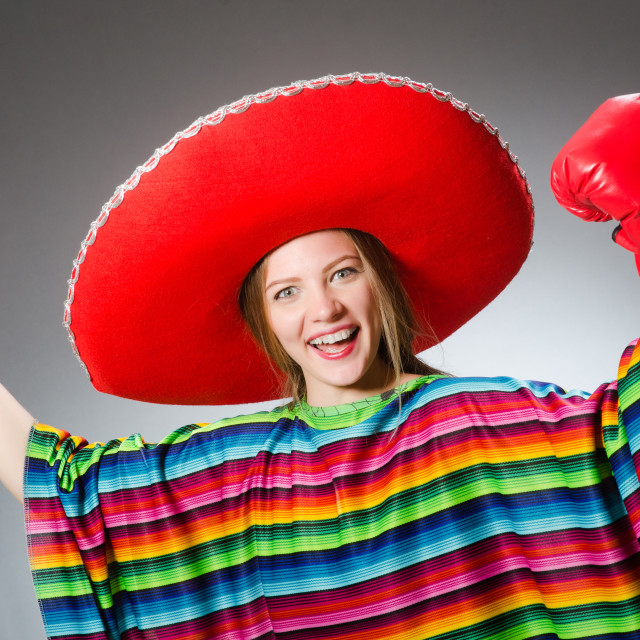 """Girl in mexican vivid poncho and box gloves against gray"" stock image"