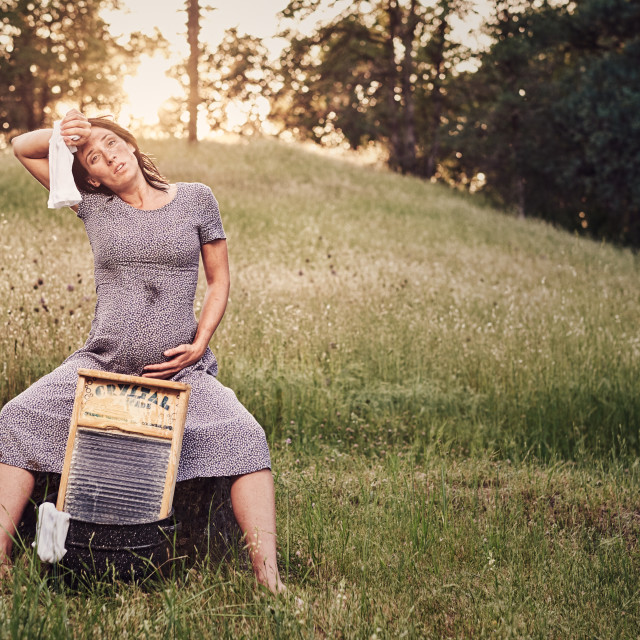 """Pregnant Woman Washing Clothes on a Washboard"" stock image"