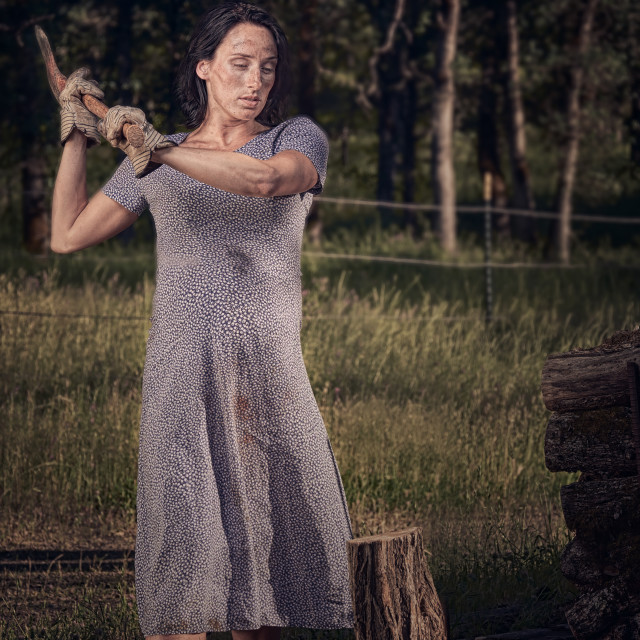 """A Pregnant Woman in a Vintage Dress Chopping Wood"" stock image"