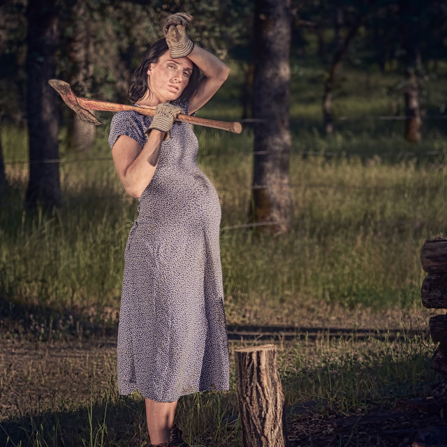 """A Pregnant Woman Resting After Chopping Wood"" stock image"
