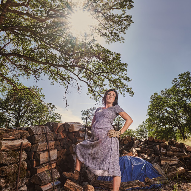 """A Pregnant Woman Resting After Stacking Wood."" stock image"