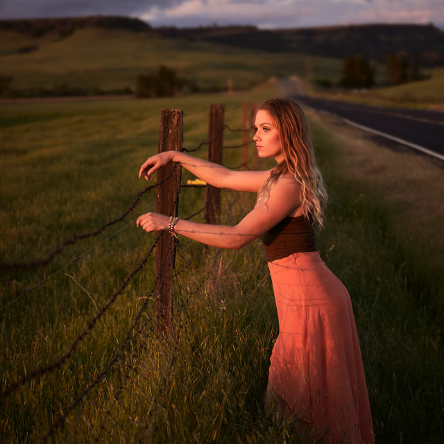 """Young Woman in a Long Skirt Leaning on a Cattle Ranch Fence."" stock image"