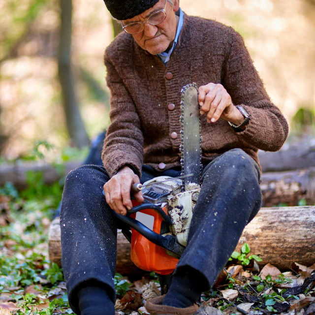 """Old man servicing his chainsaw"" stock image"