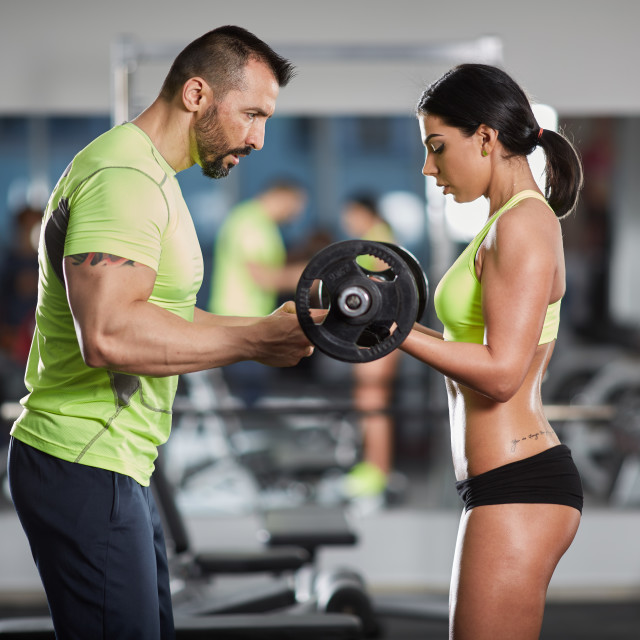 """""""Trainer helping with biceps curl"""" stock image"""
