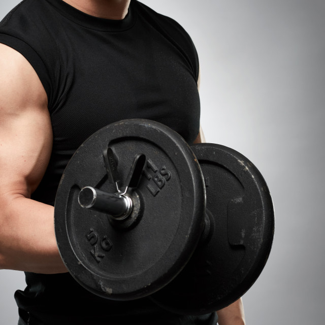 """""""Biceps curl with dumbbell on grey background"""" stock image"""