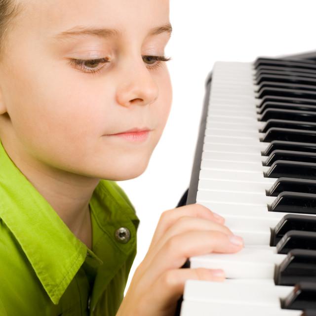 """Cute kid playing piano"" stock image"