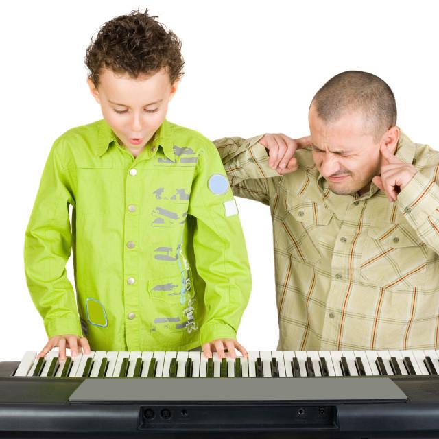 """Kid playing piano badly"" stock image"
