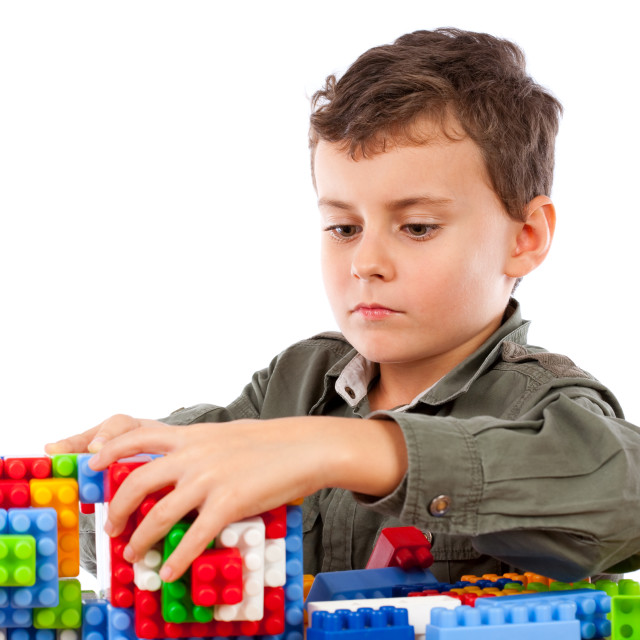 """Little boy playing with plastic cubes"" stock image"