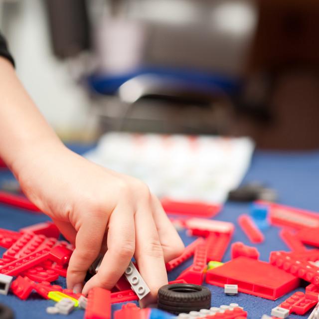 """Boy's hand picking plastic toys"" stock image"