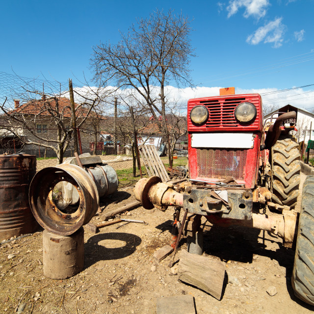 """Beaten up old tractor in the countryside, on a jack"" stock image"