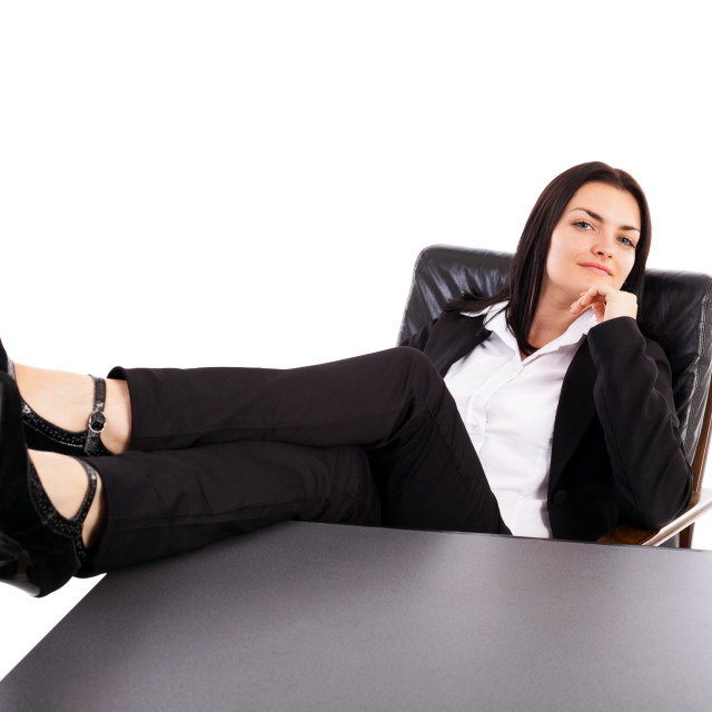 """""""Young businesswoman sitting in an armchair with legs on table"""" stock image"""