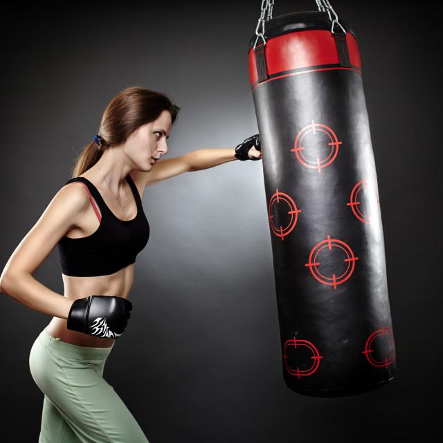 """Woman hitting the punching bag"" stock image"