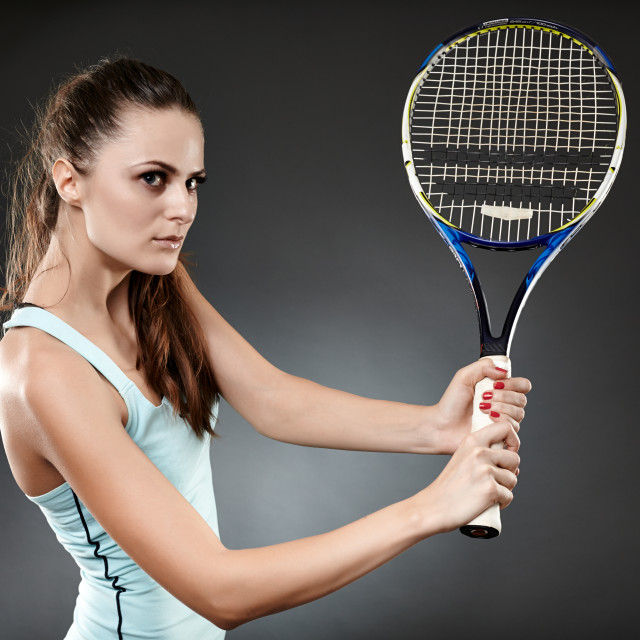 """Female tennis player with racket executing volley"" stock image"