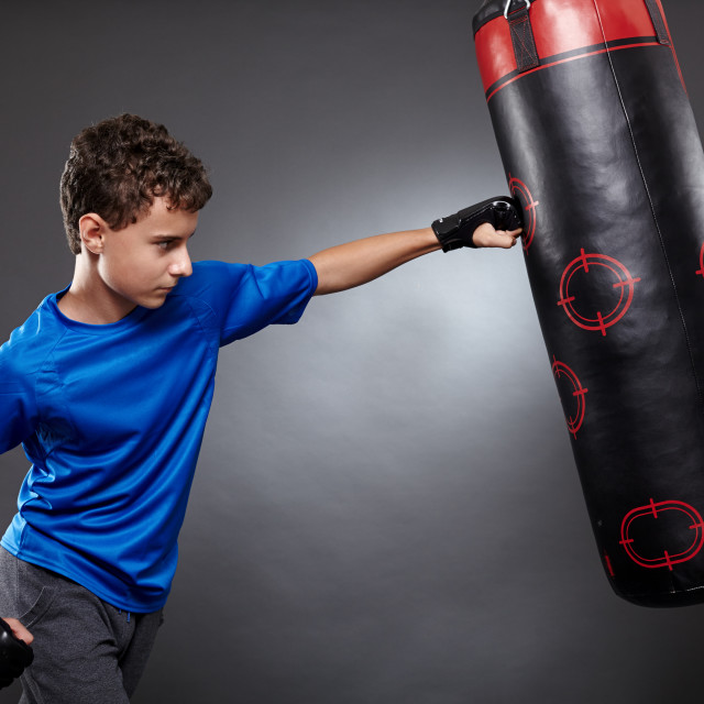 """Boy hitting the punching bag"" stock image"