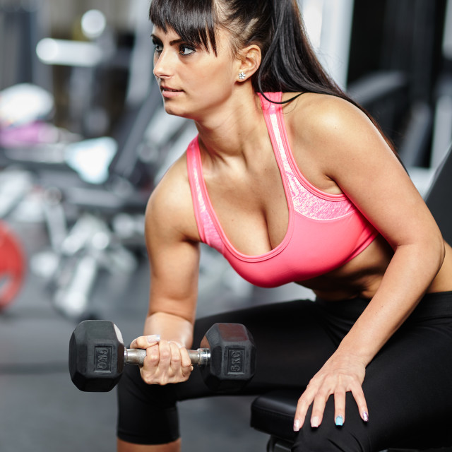 """""""Girl doing biceps workout in a gym"""" stock image"""