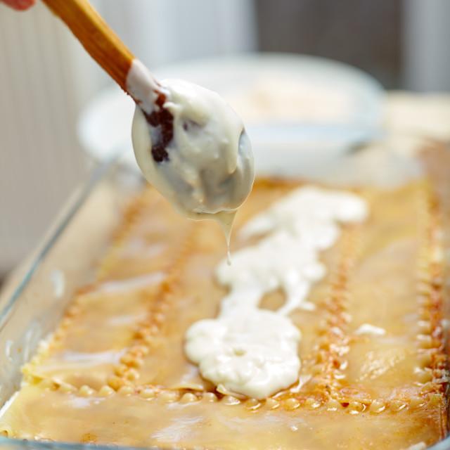 """Adding bechamel sauce to lasagna recipe"" stock image"