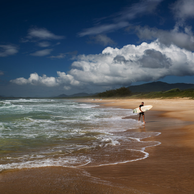 """A surfer makes his way out of the ocean on praia da Mocambique beach during the day on Florianopolis island in Santa Catarina state, Brazil."" stock image"