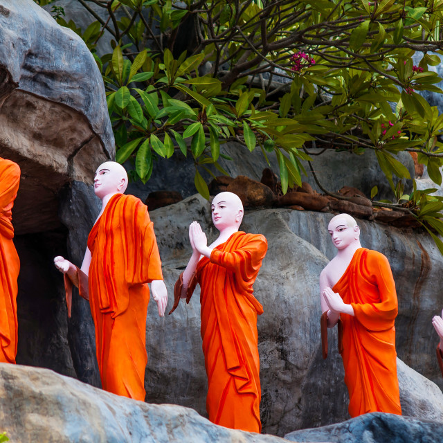 """Row of Buddhist Monk statues in orange monastic robes"" stock image"