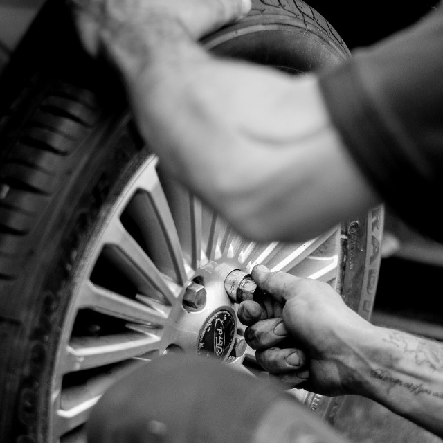 """Close up on hands placing wheel nut"" stock image"