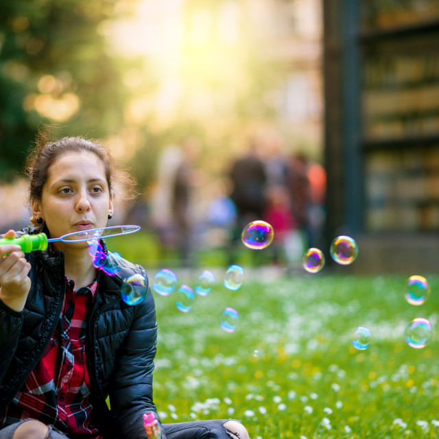 """Happy young woman with beautiful smile is blowing bubbles"" stock image"