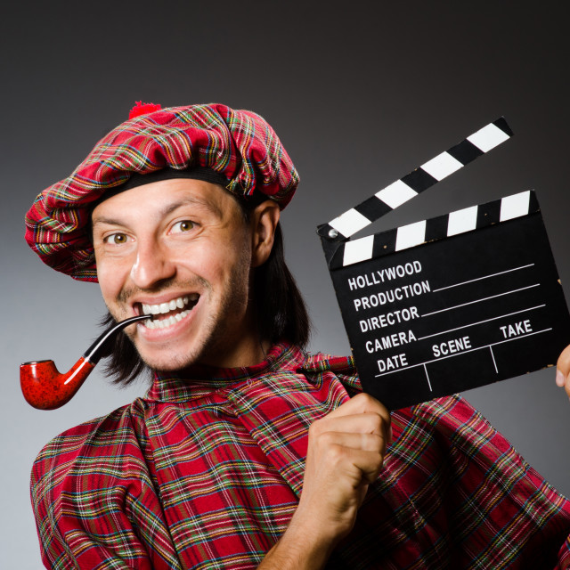 """""""Funny scotsman with movie board and smoking pipe"""" stock image"""