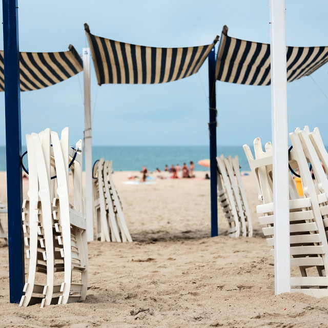 """Folded chairs and sunshades"" stock image"