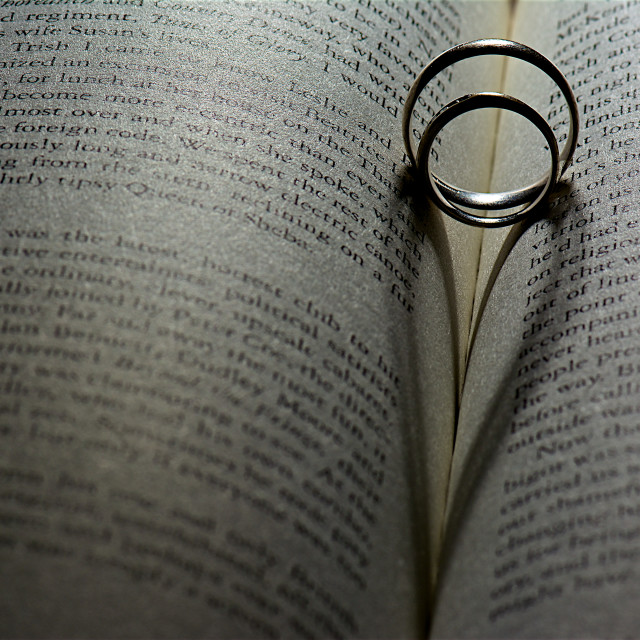"""Ring of hearts. wedding rings with heart shadow on book"" stock image"