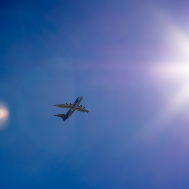 """Overhead plane with lens flare"" stock image"