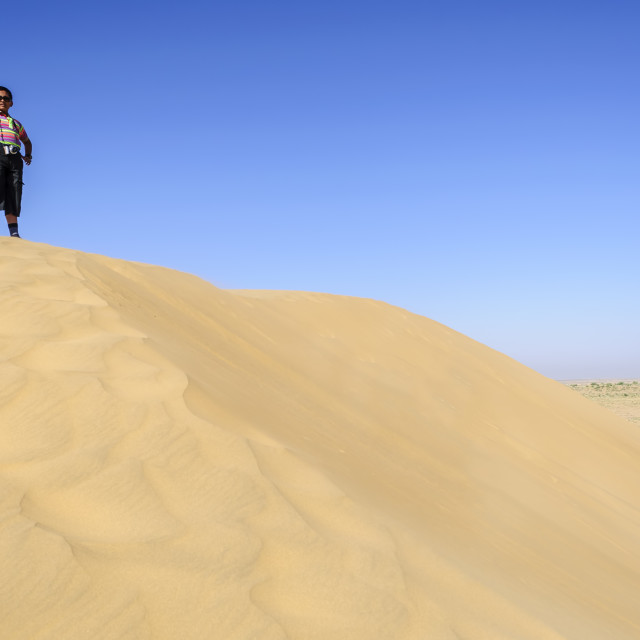 """Indian boy, tourist, with binoculars, standing on sand dune of"" stock image"