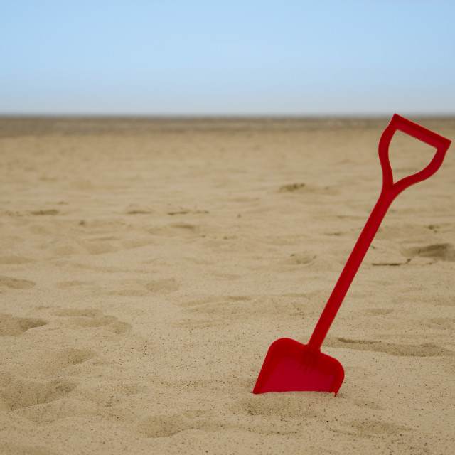 """Single Red Spade in Sand"" stock image"