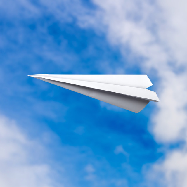 """Paper plane in blue sky, escape from it all."" stock image"