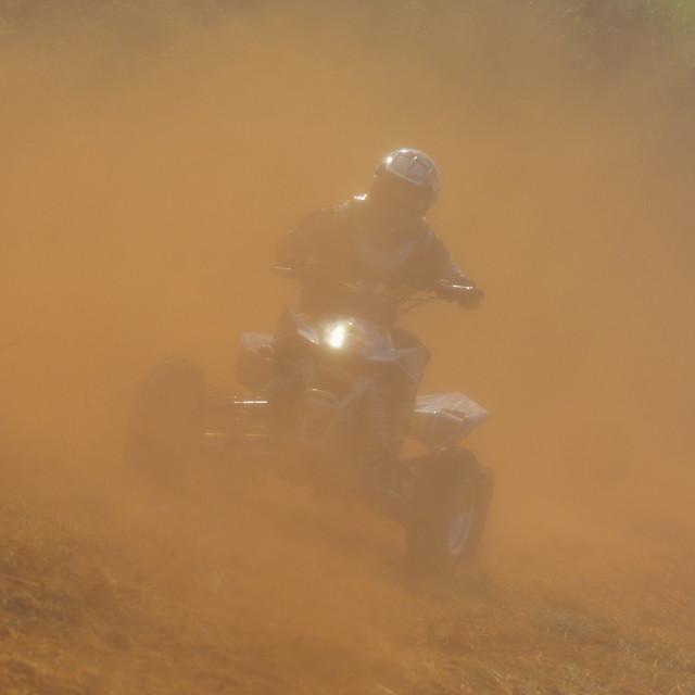 """ATV rider in helmet riding in dust."" stock image"