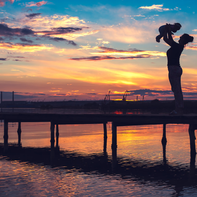 """Mother and little baby having fun at sunset"" stock image"