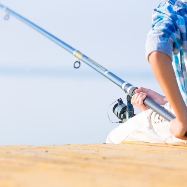 """Close-up of hands of a boy with a fishing rod"" stock image"