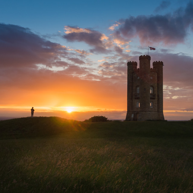 """Walker silhouetted by sunset at Broadway Tower"" stock image"