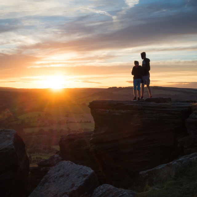 """Youngsters enjoying the sunset on a cliff top in the Peak District"" stock image"
