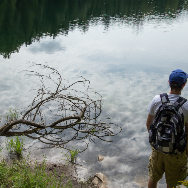 """Man looking into reflective lake"" stock image"