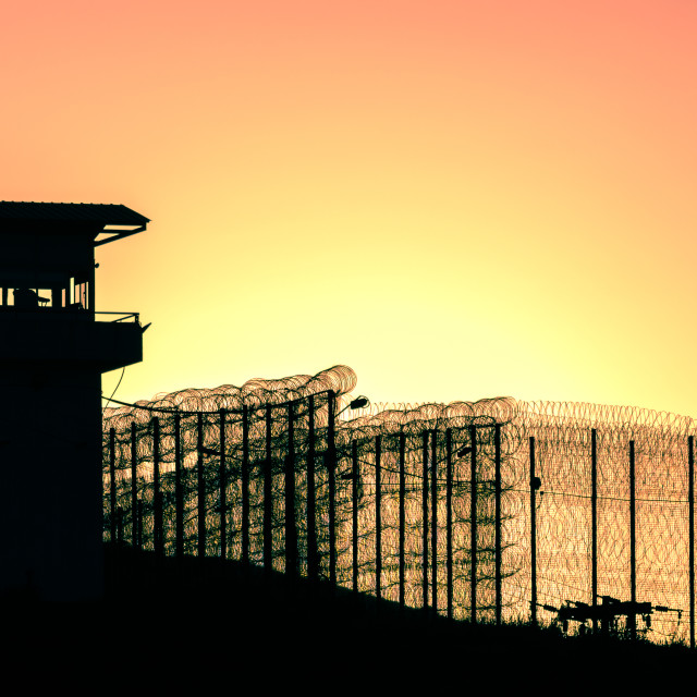 """""""Silhouette of barbed wires and watchtower of prison"""" stock image"""