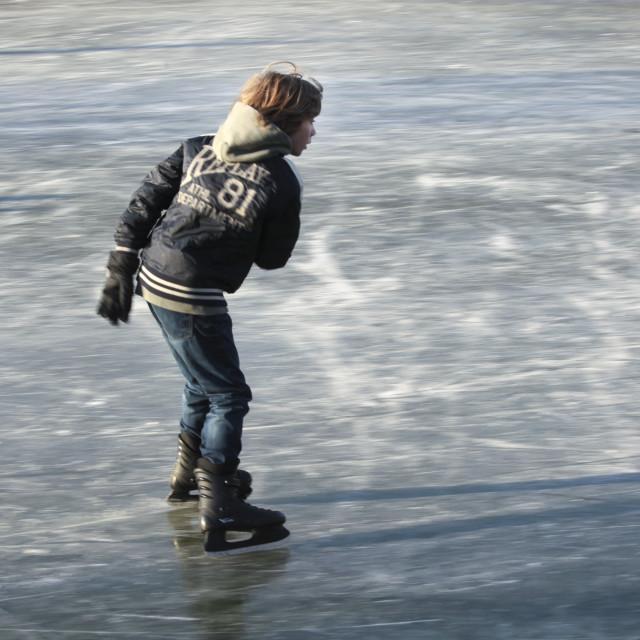 """Boy skating on natural ice"" stock image"