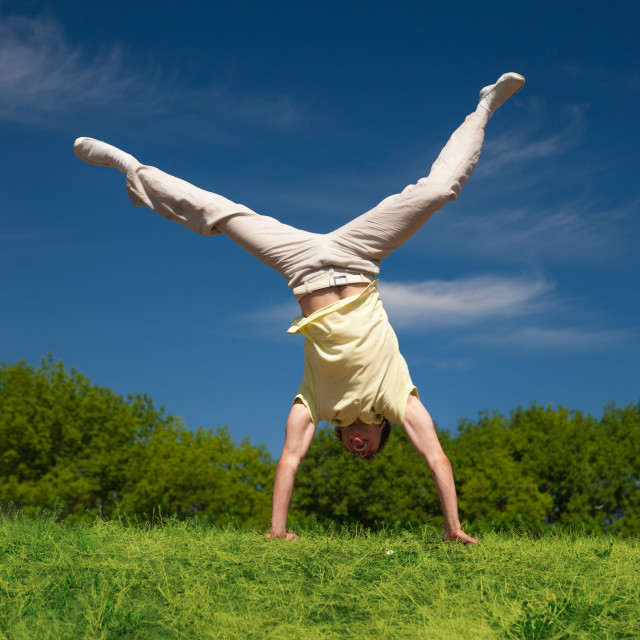 """Young man jump on hill in park"" stock image"