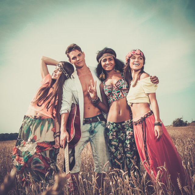 """Multi-ethnic hippie friends with guitar in a wheat field"" stock image"