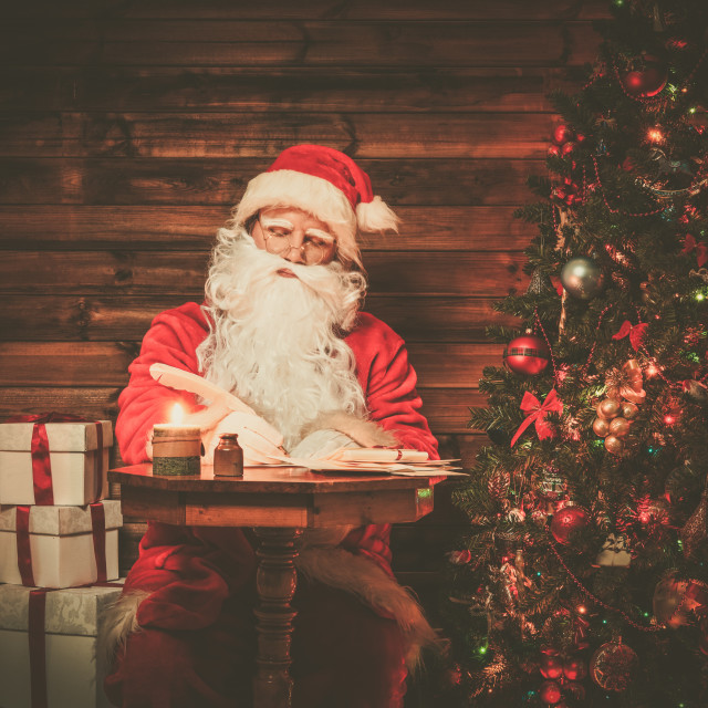 """Santa Claus in wooden home interior sitting behind table and writing letters..."" stock image"