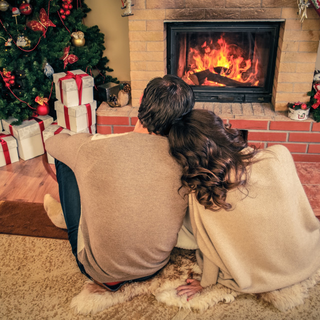 """Couple near fireplace in Christmas decorated house interior"" stock image"