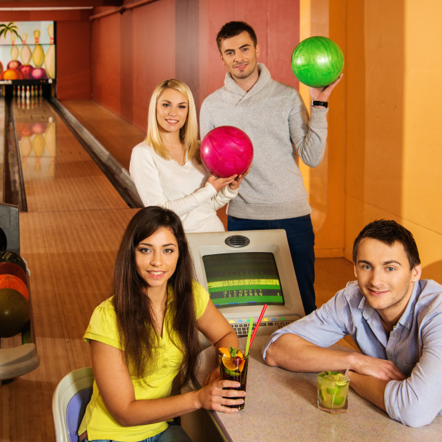 """Group of young people behind table in bowling club"" stock image"