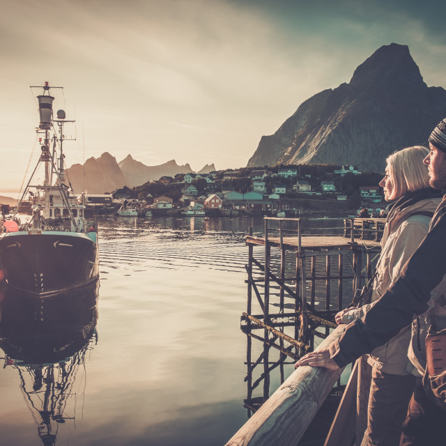 """Young travellers couple looking at sunset in Reine village, Norway"" stock image"