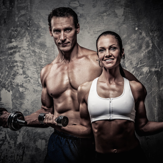 """Athletic man and woman with a dumbbells"" stock image"