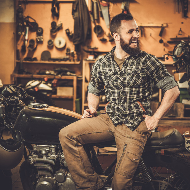 """Rider and his vintage style cafe-racer motorcycle in customs garage"" stock image"
