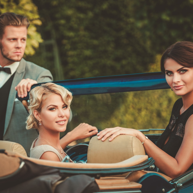 """Wealthy friends in a classic convertible"" stock image"