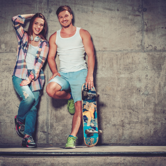 """Young couple with skateboard outdoors"" stock image"