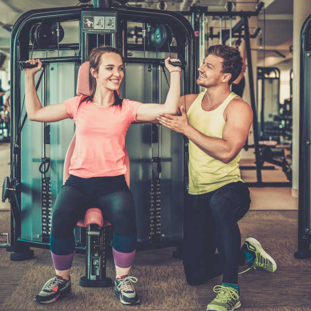 """Trainer explaining how to use training machine in a gym"" stock image"